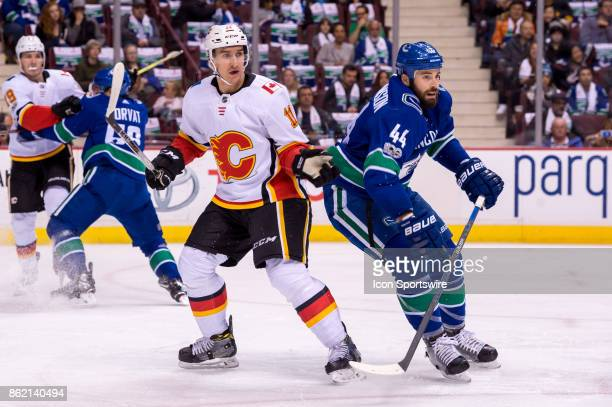 Vancouver Canucks Defenceman Erik Gudbranson defends against Calgary Flames Center Mikael Backlund during their NHL game at Rogers Arena on October...