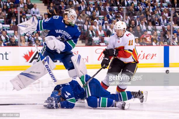 Vancouver Canucks Defenceman Erik Gudbranson is checked to the ice by Calgary Flames Center Mikael Backlund in front of Vancouver Canucks Goalie...
