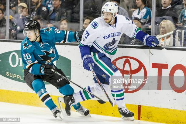 Vancouver Canucks defenseman Alexander Edler and San Jose Sharks right wing Marcus Sorensen behind the Vancouver Canucks net during the first period...