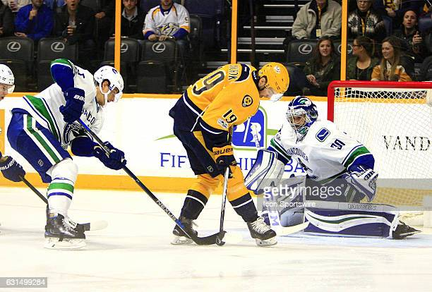 Vancouver Canucks defenseman Luca Sbisa defends as Nashville Predators winger Calle Jarnkrok tries to gain control of the puck in front of Vancouver...