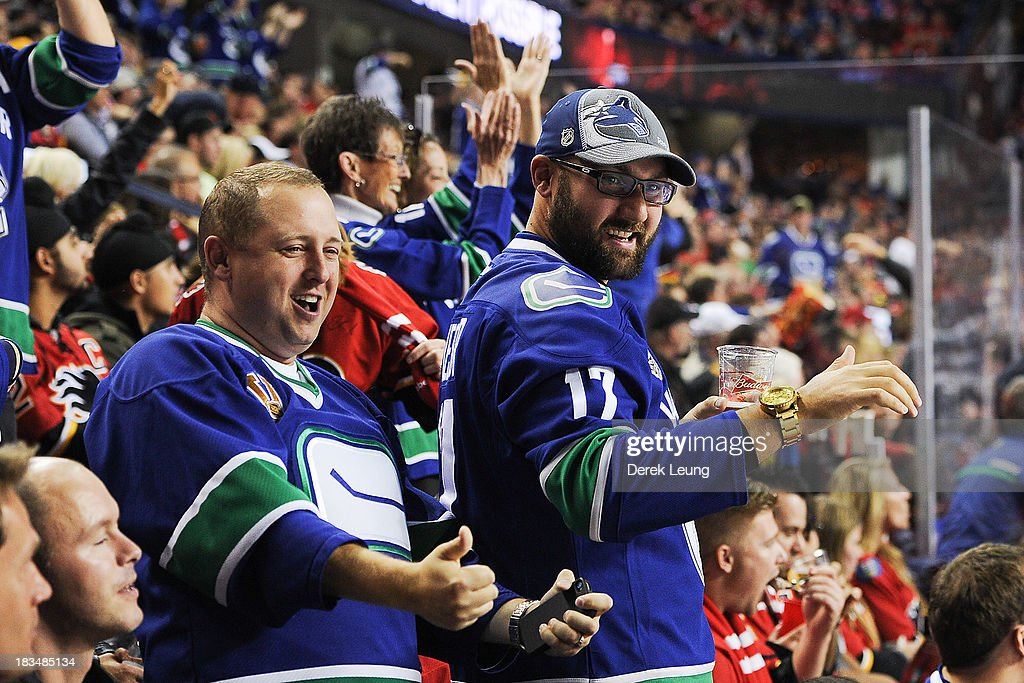 Vancouver Canucks fans celebrate a Canucks goal against the Calgary Flames during the Flames' home opening NHL game at Scotiabank Saddledome on October 6, 2013 in Calgary, Alberta, Canada. The Vancouver Canucks won 5-4 in OT.