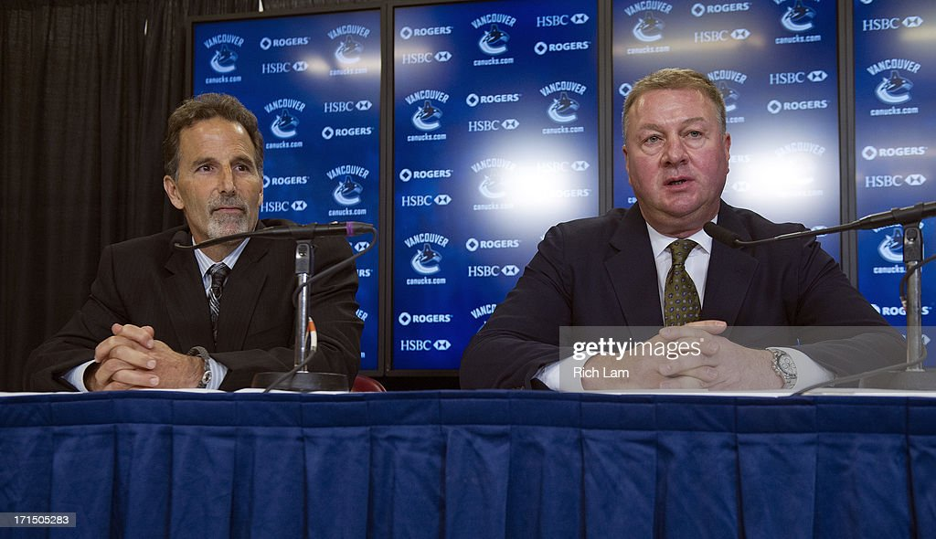 Vancouver Canucks General Manager Mike Gillis (R) introduces head coach John Tortorella during a press conference, June 25, 2013 at Rogers Arena in Vancouver, British Columbia, Canada.
