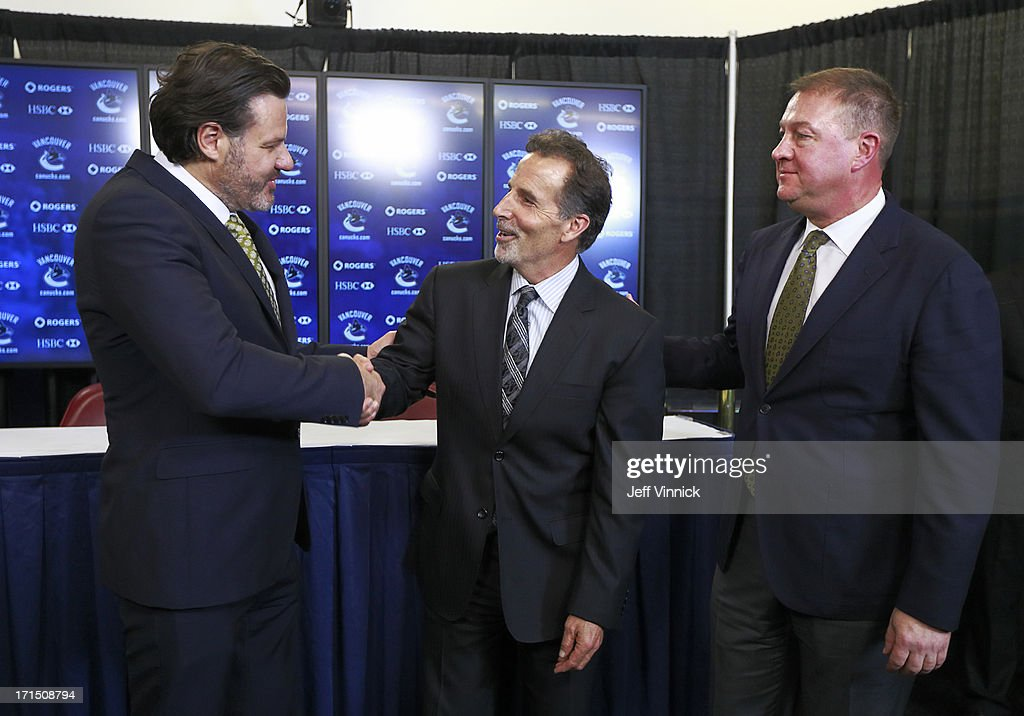 Vancouver Canucks General Manager Mike Gillis (R) looks on as Canucks owner Francesco Aquilini (L) shakes hands with new head coach John Tortorella during a press conference at Rogers Arena June 25, 2013 in Vancouver, British Columbia, Canada.