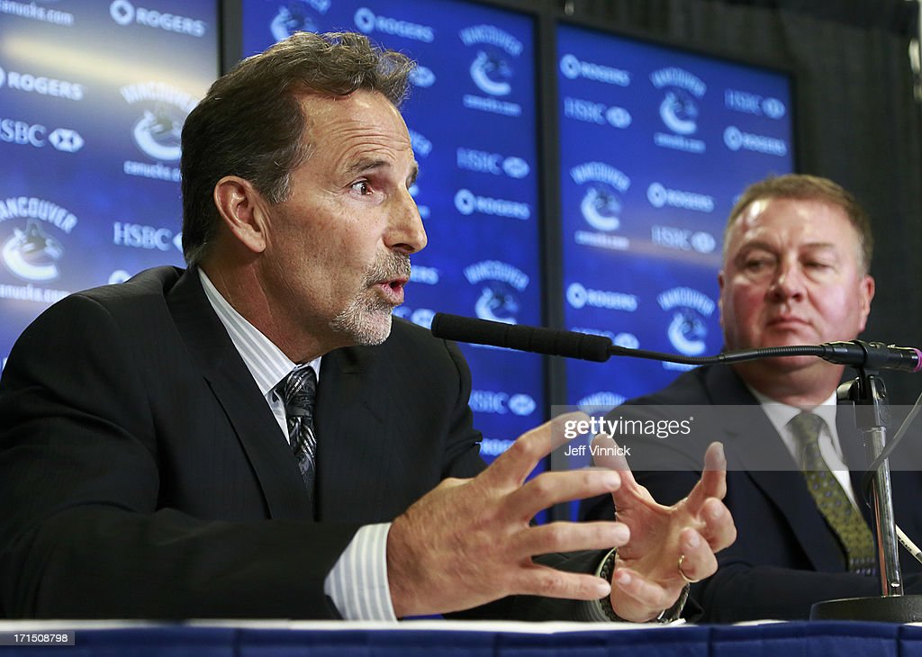 Vancouver Canucks General Manager Mike Gillis (R) looks on as new Canucks head coach John Tortorella talks during a press conference at Rogers Arena June 25, 2013 in Vancouver, British Columbia, Canada.