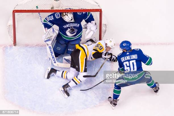Vancouver Canucks Goalie Jacob Markstrom sits in the net after colliding with Pittsburgh Penguins Left Wing Jake Guentzel during their NHL game at...