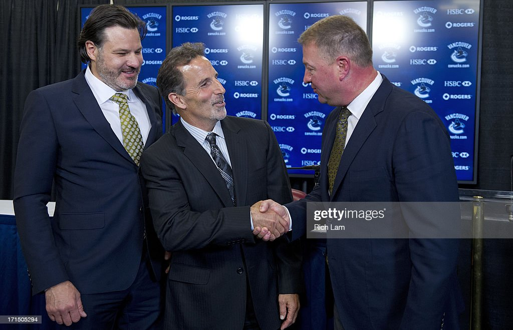 Vancouver Canucks head coach John Tortorella shakes hands with General Manager Mike Gillis as team owner Francesco Aquilini looks on after a press conference announcing him as the new head coach of the team, June 25, 2013 at Rogers Arena in Vancouver, British Columbia, Canada.