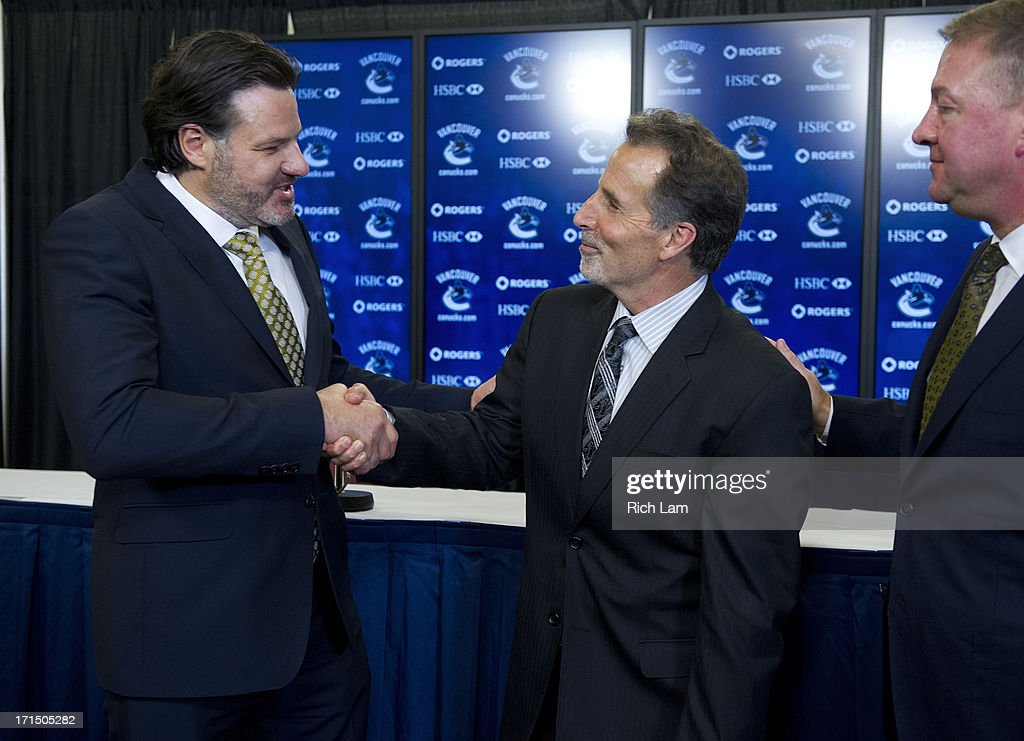 Vancouver Canucks head coach John Tortorella shakes hands with team owner Francesco Aquilini as General Manager Mike Gillis looks on after a press conference announcing him as the new head coach of the team, June 25, 2013 at Rogers Arena in Vancouver, British Columbia, Canada.