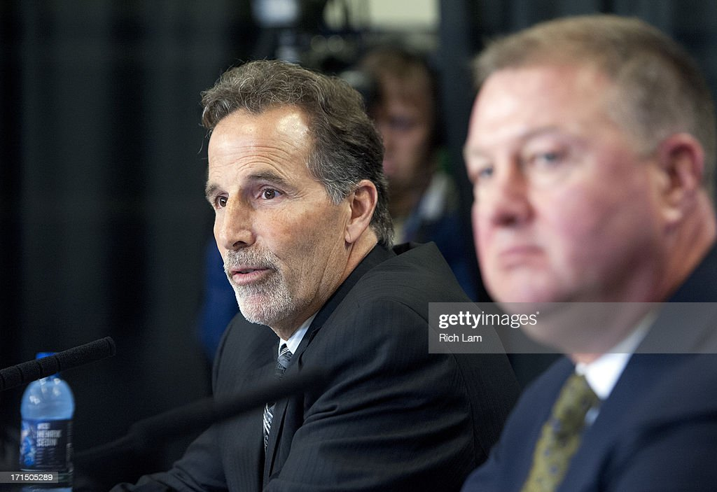 Vancouver Canucks head coach John Tortorella (L) speaks while General Manager Mike Gillis looks on during a press conference announcing him as the new head coach of the team, June 25, 2013 at Rogers Arena in Vancouver, British Columbia, Canada.