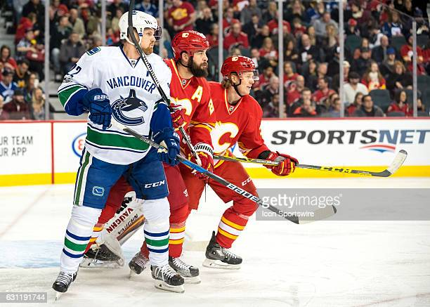 Vancouver Canucks Left Wing Daniel Sedin Calgary Flames Defenceman Deryk Engelland and Calgary Flames Defenceman Jyrki Jokipakka keep position in...