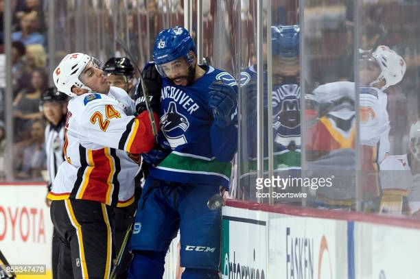 Vancouver Canucks left wing Darren Archibald is checked by Calgary Flames defenseman Travis Hamonic during their NHL preseason game at Rogers Arena...