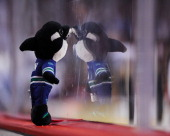 Vancouver Canucks mascot is placed against the plexiglass by a young fan during the Canucks' game against the Calgary Flames at Scotiabank Saddledome...