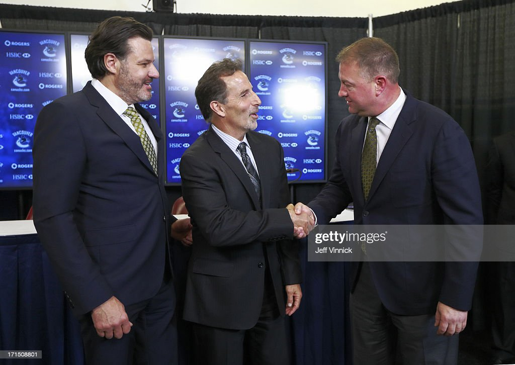 Vancouver Canucks owner Francesco Aquilini (L) looks on as new Canuck head coach John Tortorella shakes hands with Canucks General Manager Mike Gillis during a press conference at Rogers Arena June 25, 2013 in Vancouver, British Columbia, Canada.