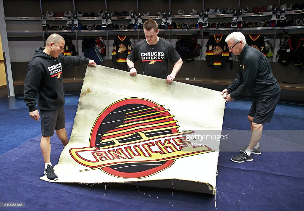 Vancouver Canucks trainers (L-R) Ferdie De Guzman, Mac Stewart and Ron Shute lay down a 20 year-old retro carpet in the Canucks dressing room before their NHL game against the Toronto Maple Leafs at Rogers Arena February 13, 2016 in Vancouver, British Columbia, Canada.