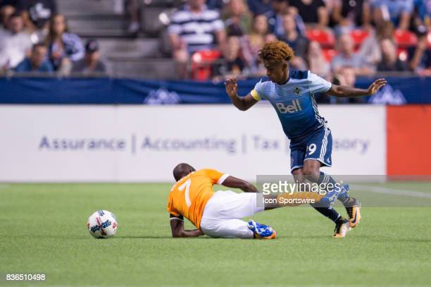 Vancouver Whitecaps forward Yordi Reyna is tripped by Houston Dynamo midfielder DaMarcus Beasley during their match at BC Place on August 19 2017 in...