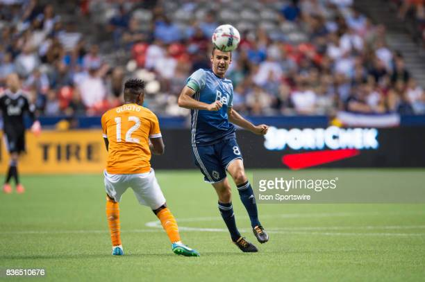 Vancouver Whitecaps midfielder Andrew Jacobson runs past Houston Dynamo forward Romell Quioto during their match at BC Place on August 19 2017 in...