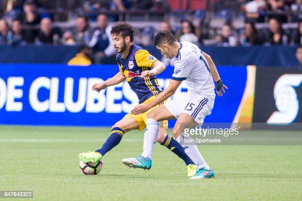 Vancouver Whitecaps midfielder Matias Laba defends against New York Red Bulls midfielder Felipe Martins during the CONCACAF Champions League...