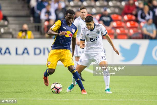 Vancouver Whitecaps midfielder Matias Laba defends against New York Red Bulls midfielder Derrick Etienne during the CONCACAF Champions League...