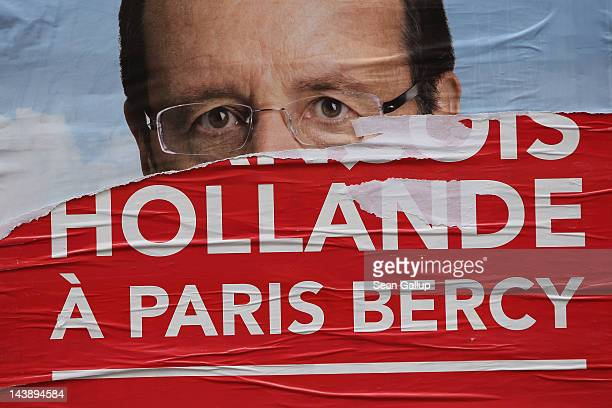 A vandalized election poster showing French Socialist presidential election candidate Francois Hollande hangs on a wall in a street the day before...