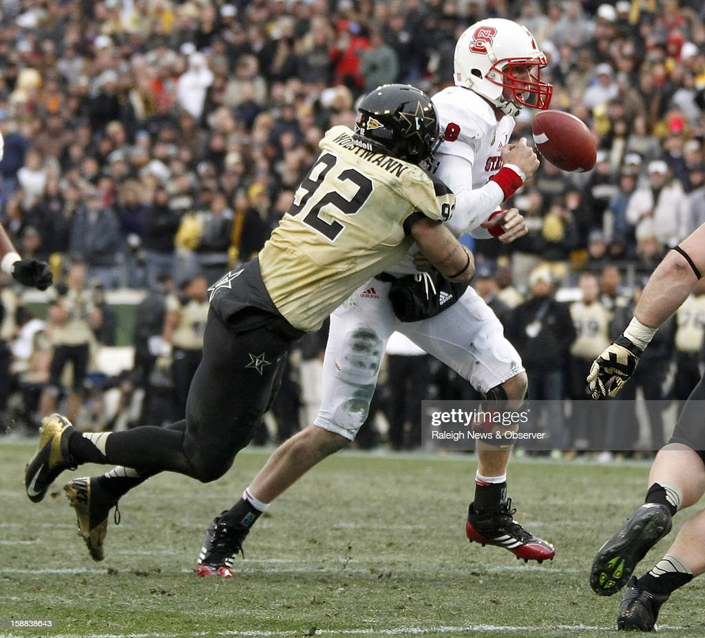 Vanderbilt defensive end Kyle Woestmann (92) hits N.C. State quarterback Mike Glennon (8), causing him to fumble during the second half of N.C. State's 38-24 loss to Vanderbilt in the Franklin American Mortgage Music City Bowl at LP Field in Nashville, Tennessee, Monday, December 31, 2012.