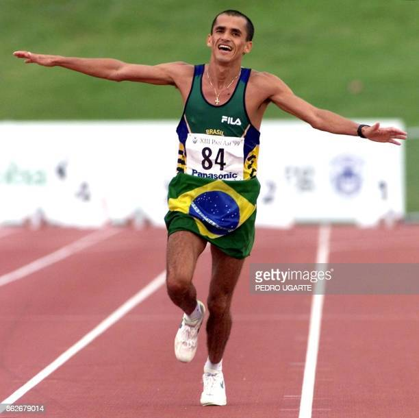 Vanderlei Lima of Brazil puts his arms out as he crosses the finish line in the mens Marathon 25 July 1999 during the 1999 Pan Am Games at the...