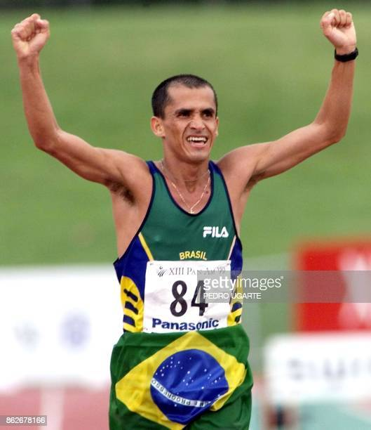 Vanderlei Lima of Brazil raises his arms in victroy as he crosses the finish line in the mens Marathon 25 July 1999 during the 1999 Pan Am Games at...