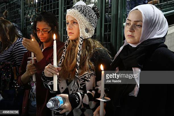 Vanessa Daley Fatimah Mardini and Najwa Mardini hold candles as they attend a vigil at the San Manuel Stadium to remember those injured and killed...