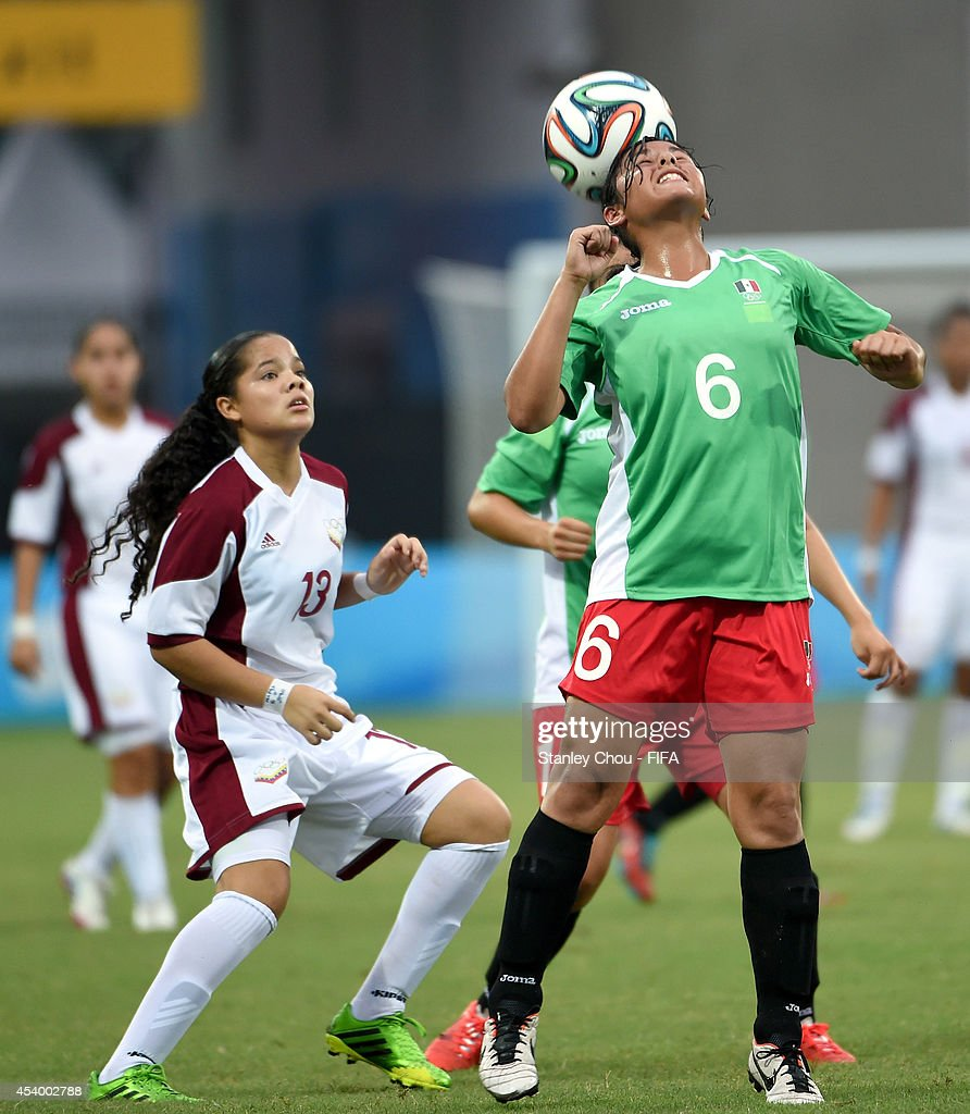 Vanessa Gonzalez of Mexico competes with Estefania Sequera of Venezuela during the 2014 FIFA Girls Summer Youth Olympic Football Tournament Semi Final match between Venezuela and Mexico at Wutaishan Stadium on August 23, 2014 in Nanjing, China.