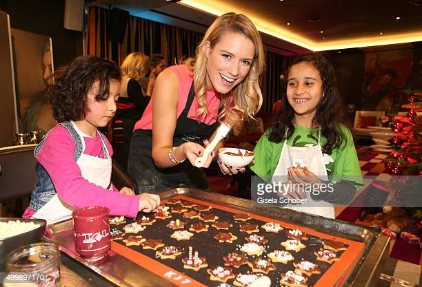 Vanessa Meisinger prepares cookies with children during the World Childhood Foundation Baking at Hotel Vier Jahreszeiten on November 30 2015 in...