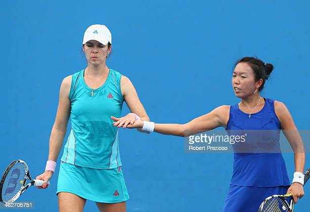 Vania King of the United States and Galina Voskoboeva of Kazakhstan talk tactics in their first round doubles match against Sandra Klemenschits of...