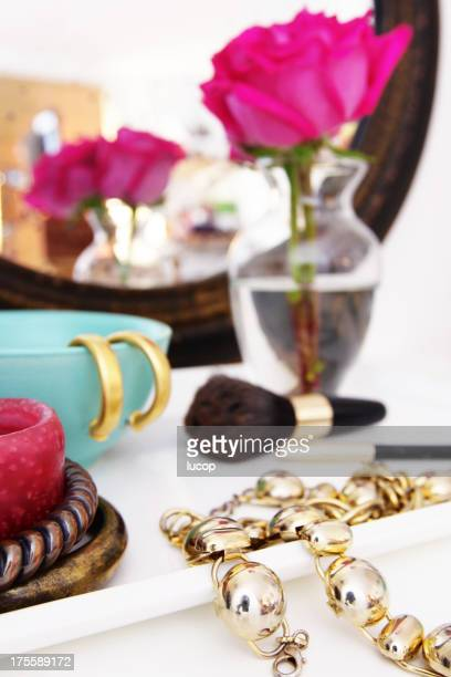 Vanity table with jewelry pieces and pink rose on vase