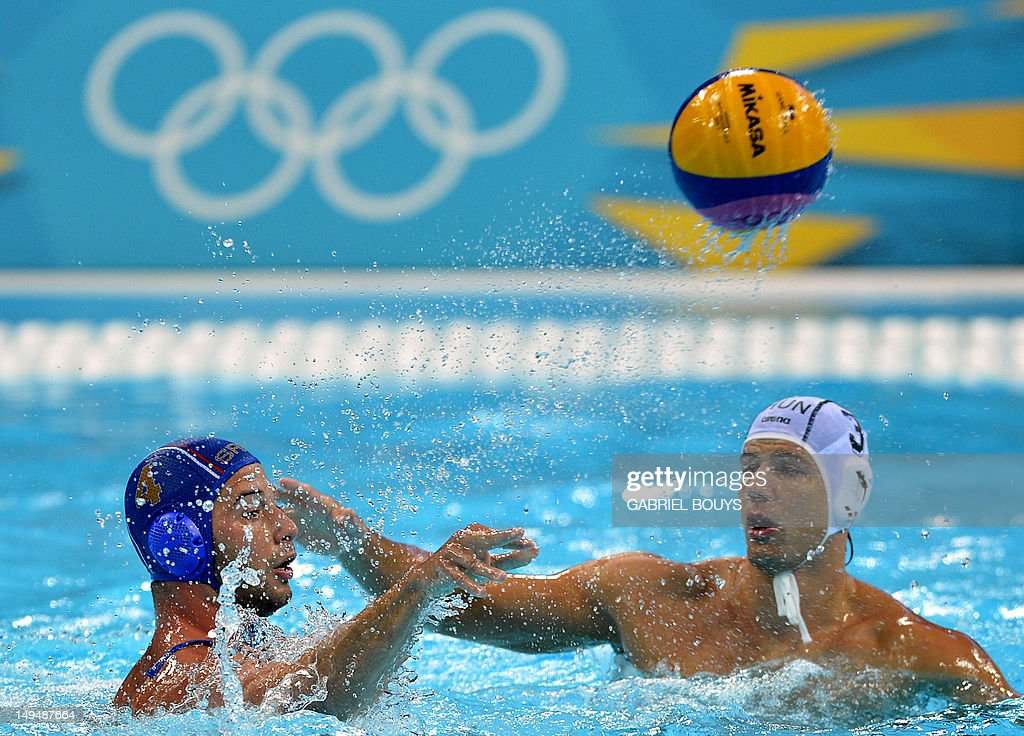 Vanja Udovicic of Serbia passes the ball in front of Nobert Madragas of Hungary during the Water Polo Group B preliminary match Hungary vs Serbia of...