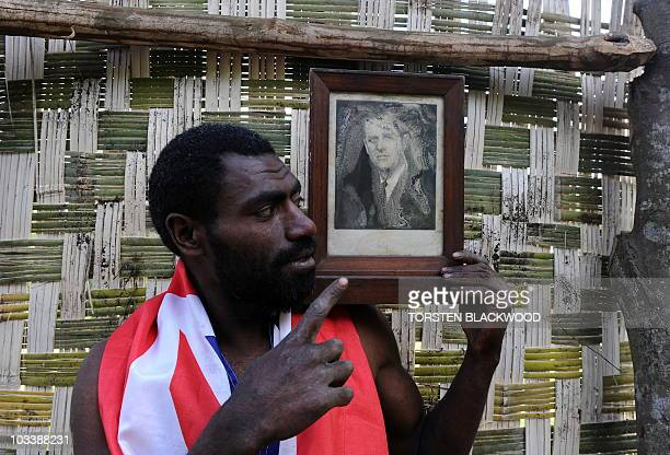 STORY 'VanuatuBritainreligionroyalsFEATURE' by Madeleine Coorey Sikor Natuan the son of the local chief holds a water damaged portrait of Britain's...
