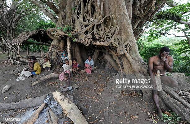 STORY 'VanuatuBritainreligionroyalsFEATURE' by Madeleine Coorey Sikor Natuan and members of his tribe sit under the banyan tree used for kava...