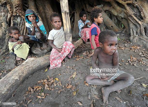 STORY 'VanuatuBritainreligionroyalsFEATURE' by Madeleine Coorey Tannese children sit under the banyan tree used for kava ceremonies in the remote...
