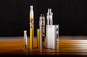 Popular vaping e cig devices mod.electronic cigarette over a wood background. vaporizer e-cig old device model.