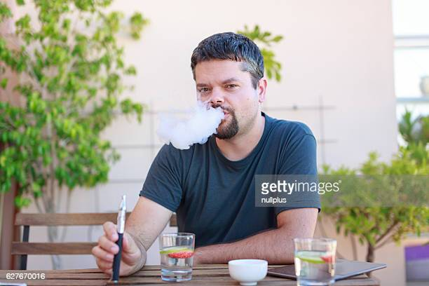 Vaping adult man, enjoying his electronic cigarette