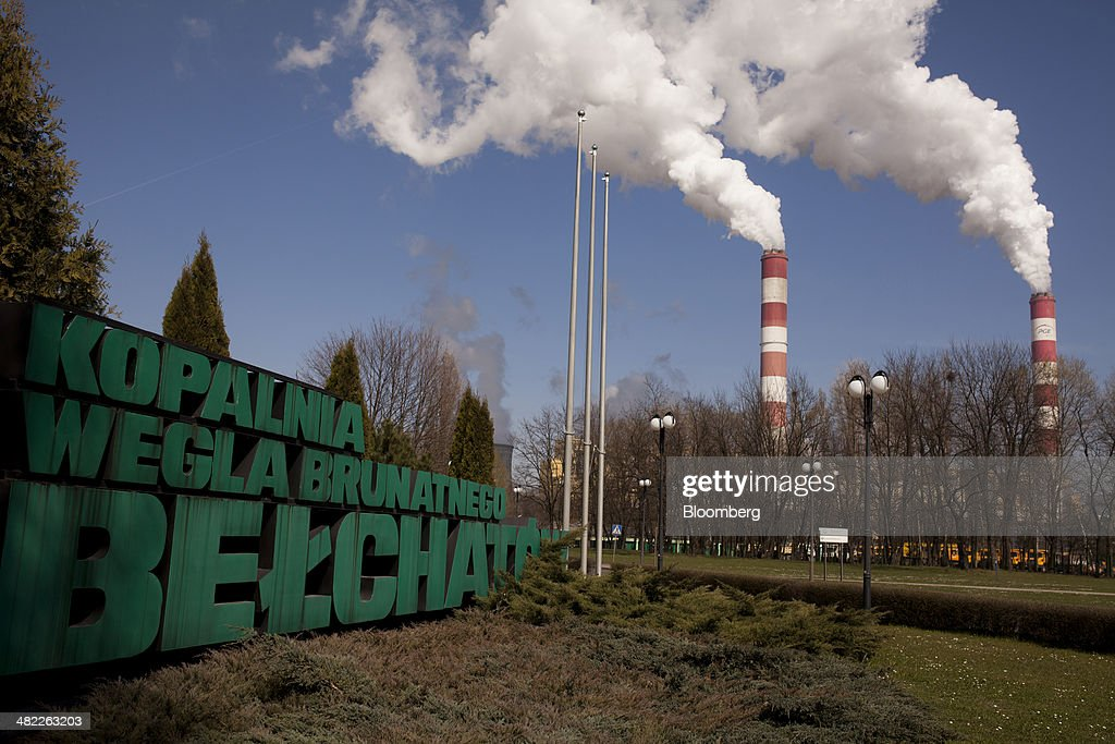 Vapor escapes from chimneys beyond an entrance sign at the lignite coal-fired power plant operated by PGE Elektrownia Belchatow SA near Belchatow, Poland, on Wednesday, April 2, 2014. Polish power prices are set to stay above German contracts through 2015, reversing a historic discount, as the cost of keeping plants open in the eastern European nation is factored in, according to Vattenfall AB. Photographer: Bartek Sadowski/Bloomberg via Getty Images