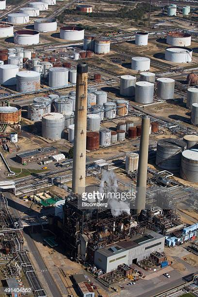 Vapor rises from plant buildings as oil storage tanks sit at the Esso oil refinery operated by Exxon Mobil Corp in Fawley UK on Friday Oct 2 2015 A...