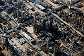 Vapor rises from plant buildings at the Esso oil refinery operated by Exxon Mobil Corp in Fawley UK on Friday Oct 2 2015 A 50 percent drop in crude...