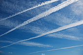 Vapour trails crossing blue sky