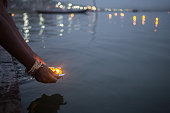 A evening shot of a woman putting blessed puja flowers in the river Ganges in Varanasi, India