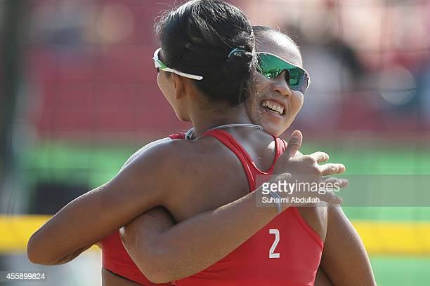 Varapatsorn Radarong and Tanarattha Udomchavee of Thailand celebrates a winning point during the Women's Beach Volleyball Preliminary Round 2014...