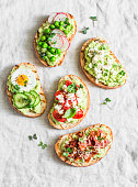 Variation avocado sandwich - with crispy bacon, quail egg, tomatoes, goat cheese, green peas, radish, cucumber. Healthy snack. On a light background, top view