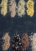 Food background. Variation of grain - quinoa, beans, rice, oatmeal, couscous, lentils, barley, oatmeal. On a dark background, top view