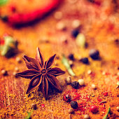 Variation of Spices and Herbs like chili peppers, rosemary, sage, peppercorns, star anise, cardamon, cayenne pepper, tumeric, cumin, fennel seeds on wooden background