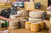 Photo captures assortment of cheeses on display at a typical french market.