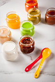 Variety of homemade baby vegetable and fruit puree,  white marble background copy space