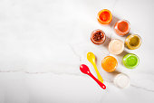 Variety of homemade baby vegetable and fruit puree,  white marble background copy space top view