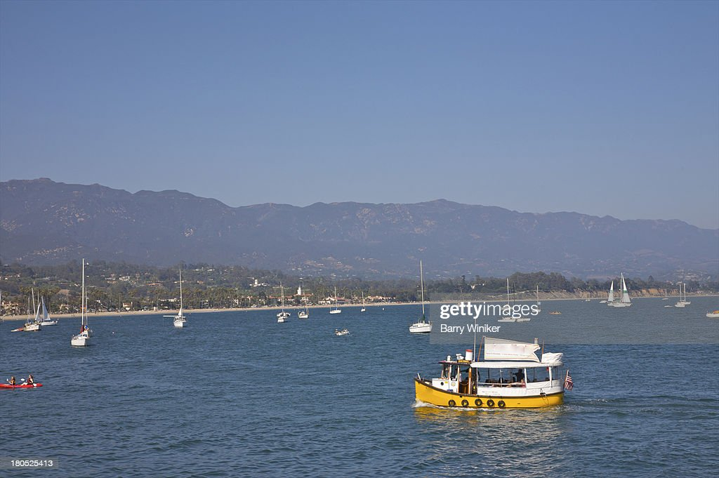 Variety of boat types in blue water near mountains