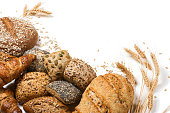 Top view of assortment of different kind of cereal bakery: bread, croissants, buns isolated on white background.